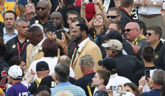 Pro Football Hall of Fame class of 2015 member Jerome Bettis, center, poses for a photo with a fan in the crowd at Tom Benson Hall of Fame Stadium while being introduced during an induction ceremony at the Pro Football Hall of Fame in Canton, Ohio, Saturday, Aug. 8, 2015. (AP Photo/Gene J. Puskar)