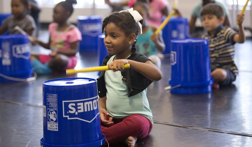 In this, Wednesday, July 29, 2015 photo, Ayannah Blanc, 6, foreground, learns how to play Haitian rara music at the Little Haiti Cultural Complex in Miami. The summer workshop is the start of a long-term program to incorporate rara and other traditional Haitian music and dance into after-school programs. (AP Photo/Wilfredo Lee)