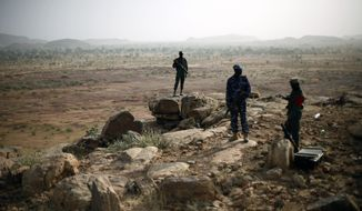 FILE - In this Thursday, Jan. 24, 2013 file photo, Malian troops man an observation post outside Sevare, some 620 kms (385 miles) north of Mali's capital Bamako. Four people held by Islamic extremists in a hotel in Sevare in central Mali were freed Saturday, Aug. 8, 2015 by the army and special forces, after fighting since Friday left a number of dead, Mali's defense ministry adviser said. (AP Photo/Jerome Delay, File)