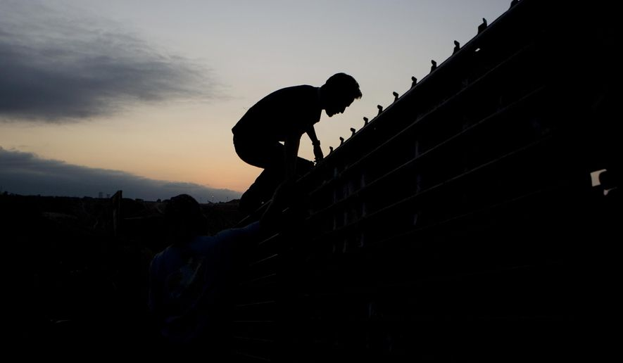 A man climbs the border wall to cross into the United States from Tijuana, Mexico, on Sept. 11, 2008. (Associated Press) **FILE**
