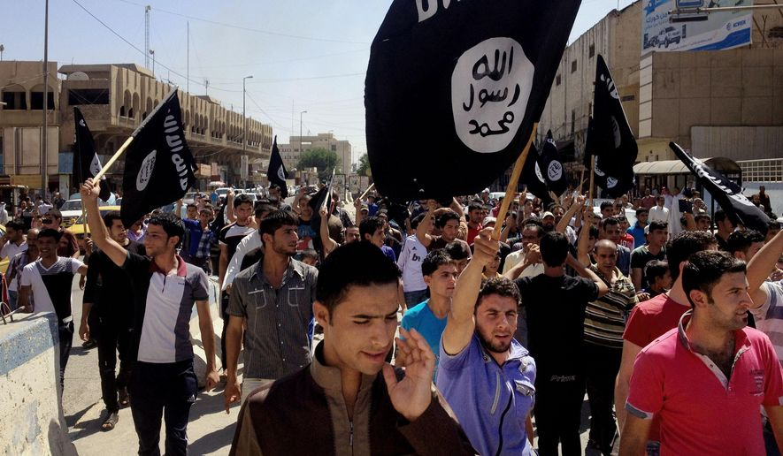 In this June 16, 2014, file photo, demonstrators chant pro-Islamic State group slogans as they carry the group's flags in front of the provincial government headquarters in Mosul, Iraq. Under its leader, Iraqi jihadi Abu Bakr al-Baghdadi, the Islamic State group top command is dominated by former officers from Saddam Hussein's military and intelligence agencies, according to senior Iraqi officers and top intelligence officials. (AP Photo, File) **FILE**