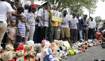 Family, friends and supporters pause for a moment of silence at a memorial to Michael Brown, Sunday, Aug. 9, 2015, in Ferguson, Mo. Sunday marks one year since Michael Brown was shot and killed by Ferguson police officer Darren Wilson. (AP Photo/Jeff Roberson)