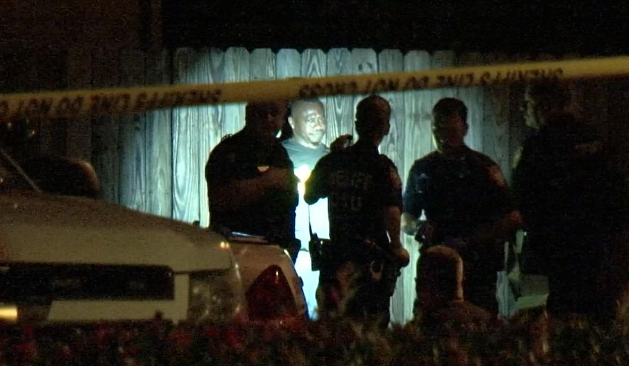 In this image made from a video, police arrest a man after he surrendered Sunday, Aug. 9, 2015, in Houston. According to authorities the bodies of multiple people including several children were found inside a Houston home following his arrest. (Photo via AP Video)