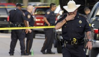 Harris County Sheriff's Department Sgt. D.J. Hilborn, right, walks away from the scene of a multiple shooting Sunday, Aug. 9, 2015, in Houston. Eight people were found dead inside a home following the arrest of David Conley, who exchanged gunfire with police, Texas authorities said Sunday. (AP Photo/David J. Phillip)