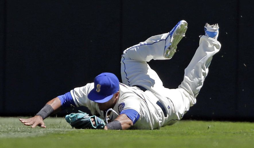 Seattle Mariners right fielder Nelson Cruz tumbles after snagging a fly ball from Texas Rangers' Delino DeShields in the first inning of a baseball game, Sunday, Aug. 9, 2015, in Seattle. (AP Photo/Elaine Thompson)