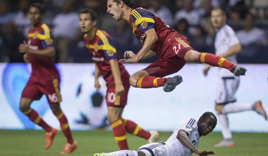 Real Salt Lake's John Stertzer, center, goes flying over Vancouver Whitecaps' Kekuta Manneh, bottom, of Gambia, after passing the ball during the second half of an MLS soccer match in Vancouver, British Columbia, on Saturday, Aug. 8, 2015. (Darryl Dyck/The Canadian Press via AP)
