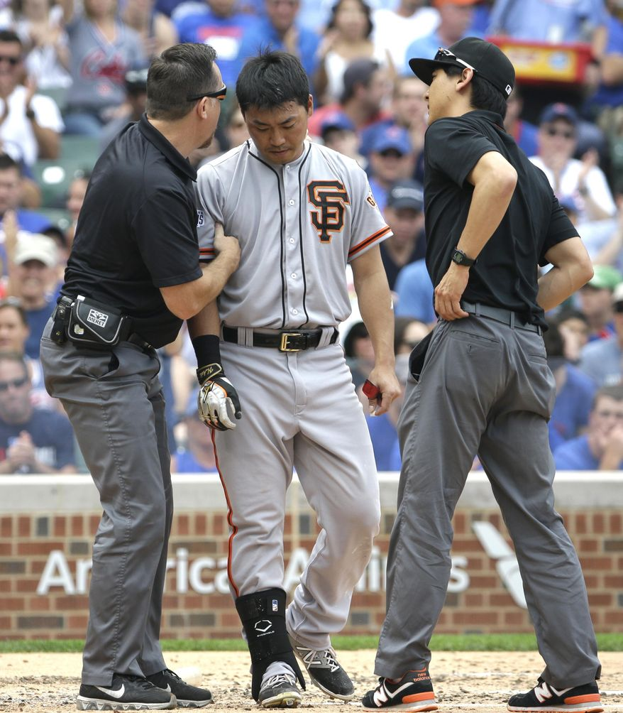 San Francisco Giants' Nori Aoki, center, of Japan, stands with trainers before leaving a baseball game after being hit by pitch during the third inning of a baseball game against the Chicago Cubs, Sunday, Aug. 9, 2015, in Chicago. (AP Photo/Nam Y. Huh)