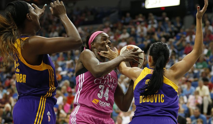 Minnesota Lynx center Sylvia Fowles (34) protects the ball against the Los Angeles Sparks center Jantel Lavender, left, and guard Ana Dabovic, right, during the second half of a WNBA basketball game, Sunday, Aug. 9, 2015, in Minneapolis. The Lynx won 72- 64. (AP Photo/Stacy Bengs)