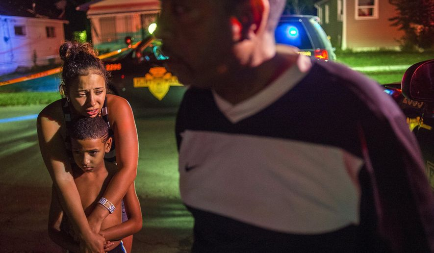Flint resident Alyssa Tyler, 25, cries as she holds her son James Tyler, 9, after learning of the death of 1-year-old Genesis General Tyler and Rita Langworthy, 70, in a double shooting as Flint Police investigate on Monday morning, Aug. 10, 2015 at the 200 block of West Home Avenue on Flint's north side. Police were called to the scene at 2:24 a.m. The double homicide brings the count to 33 in Flint so far this year. (Jake May/The Flint Journal-MLive.com via AP) LOCAL TELEVISION OUT; LOCAL INTERNET OUT; MANDATORY CREDIT