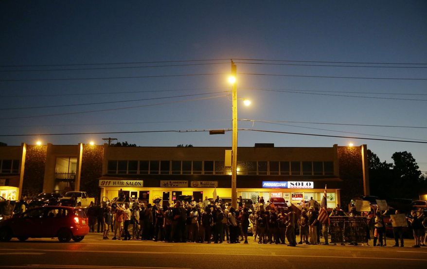 A crowd gathers along West Florissant Avenue, Monday, Aug. 10, 2015, in Ferguson, Mo. Ferguson was a community on edge again Monday, a day after a protest marking the anniversary of Michael Brown's death was punctuated with gunshots. (AP Photo/Jeff Roberson)