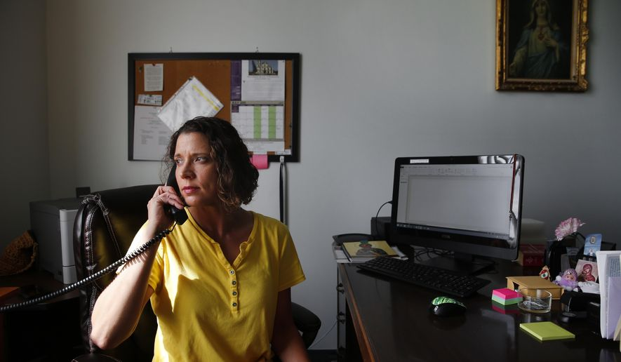 In this Monday, July 20, 2015 photo, Julie Baumer, an administrative assistant at a church parish, works in Warren, Mich. Baumer spent four years in prison until a judge tossed aside a child abuse conviction issued after doctors and prosecutors mistakenly blamed her nephew's head injuries on shaken-baby trauma. (AP Photo/Paul Sancya)
