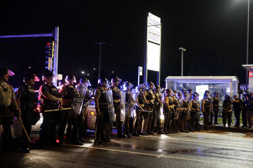 Police form a line across West Florissant Ave. during a protest Sunday in Ferguson, Mo. (Associated Press)