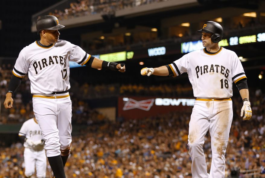 Pittsburgh Pirates' Aramis Ramirez (17) is greeted by Neil Walker after scoring on a single by Francisco Cervelli in the fifth inning of a baseball game against the Los Angeles Dodgers, Sunday, Aug. 9, 2015, in Pittsburgh. (AP Photo/Keith Srakocic)