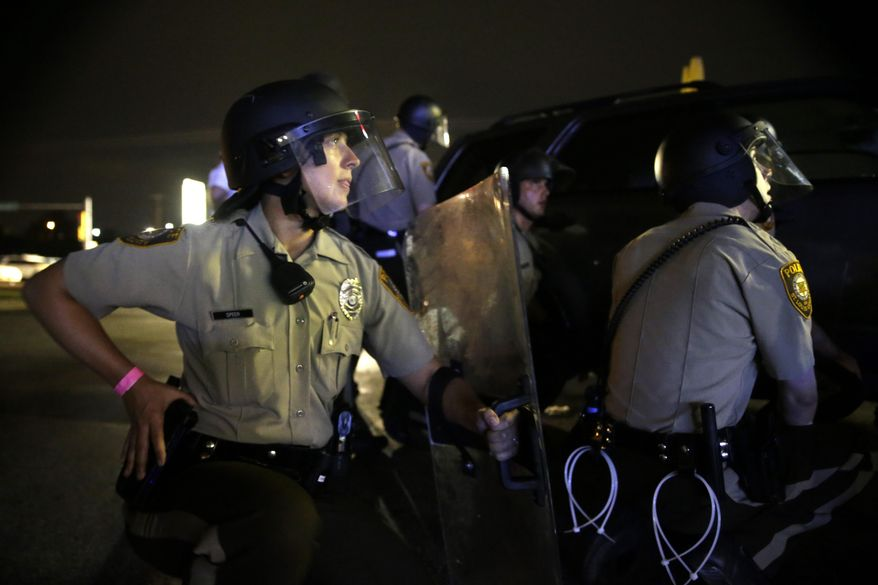 Police take cover after gunfire near a protest in Ferguson, Mo., Sunday, Aug. 9, 2015. The one-year anniversary of Michael Brown's death in Ferguson began with a march in his honor and ended with a protest that was interrupted by gunfire. (AP Photo/Jeff Roberson)
