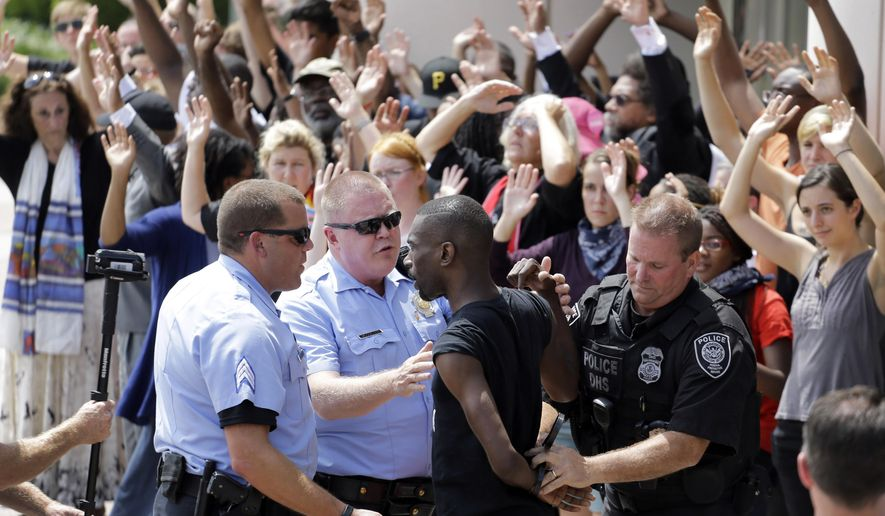 Activist DeRay McKesson is arrested by St. Louis and Federal Protective Service police outside the Thomas F. Eagleton Federal Courthouse, Monday, Aug. 10, 2015, in St. Louis. Several protesters were arrested. (AP Photo/Jeff Roberson)