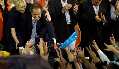 Governor of the Buenos Aires province and presidential candidate Daniel Scioli (second from left) and his wife Karina Rabolini greet followers after primary elections in Buenos Aires on Monday. Voters on Sunday began the process ahead of Oct. 25 general elections to decide presidential candidates in their respective parties. (Associated Press)