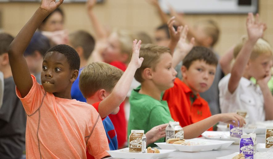 In this Thursday, Aug. 6, 2015 photo, student James Barragan, left, and other students raise their hands during lunch in the cafeteria at Hendron-Lone Oak Elementary in Paducah, Ky. Thursday was the first day of classes for all McCracken County Public Schools.(Ellen O'Nan/The Sun via AP)