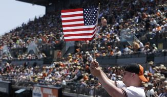 A San Francisco Giants fan waves an American flag during a baseball game between the Giants and the Oakland Athletics in San Francisco, Sunday, July 26, 2015. (AP Photo/Jeff Chiu)