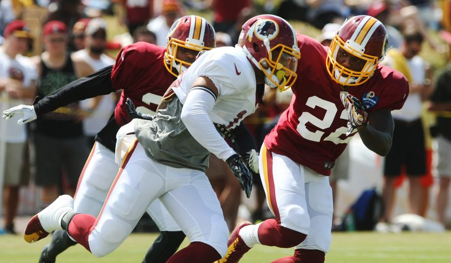 Washington Redskins wide receiver Reggie Bell, center, runs past Washington Redskins defensive back Justin Rogers, left, and Washington Redskins cornerback Everett Deshazor during the team's NFL football training camp in Richmond, Va., Monday, Aug. 3, 2015. (AP Photo/Jason Hirschfeld)