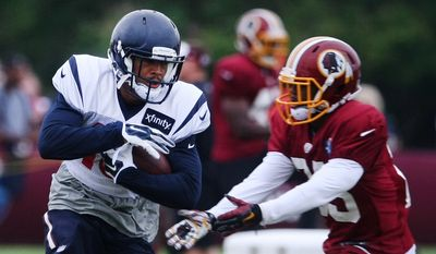 Houston Texans wide receiver Cecil Shorts III, center, shakes past Washington Redskins defensive back Justin Rogers during a joint NFL training camp in Richmond, Va., Friday, Aug. 7, 2015. (AP Photo/Jason Hirschfeld)