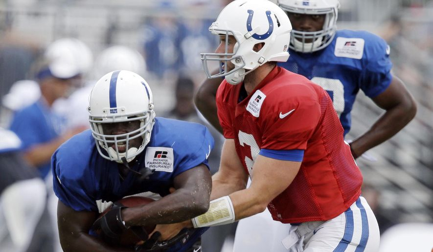 Indianapolis Colts' Frank Gore takes a handoff from quarterback Andrew Luck during NFL football training camp Monday, Aug. 10, 2015, in Anderson, Ind. (AP Photo/Darron Cummings)