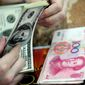 A Chinese clerk counts U.S. dollars in exchange for the Chinese renminbi at a bank in Hefei in central China's Anhui province. (Associated Press)