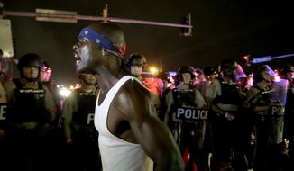 A protester yells as police form a line across West Florissant Ave., Sunday, Aug. 9, 2015, in Ferguson, Mo., before shots were fired near the protest. The one-year anniversary of Michael Brown's death in Ferguson began with a march in his honor and ended with a protest that was interrupted by gunfire. (AP Photo/Jeff Roberson)