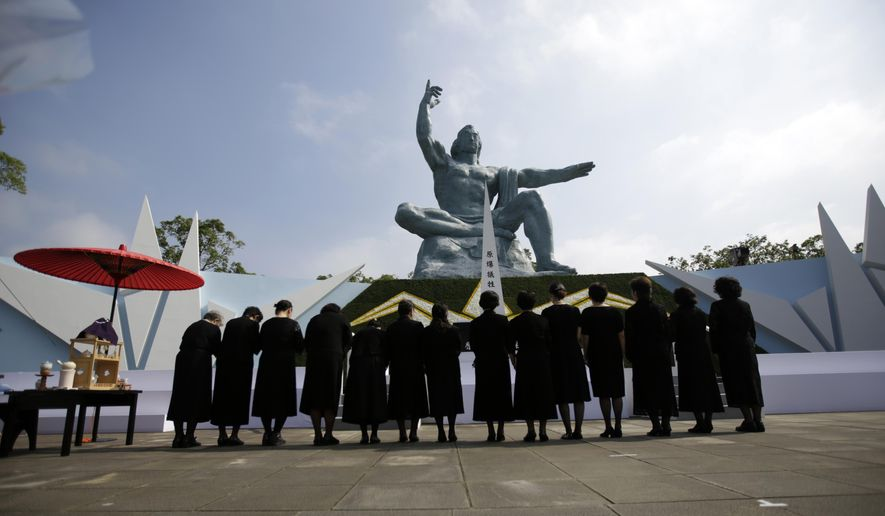 """FILE - In this Sunday, Aug. 9, 2015 file photo, visitor offer prayers in front of the Peace Statue at the 70th anniversary of the atomic bombing in Nagasaki, southern Japan. Walt Disney Japan apologized Monday, Aug. 10 after a tweet sent from its corporate Twitter account wished readers """"congratulations on a not special day"""" on the 70th anniversary of the U.S. atomic bombing of Nagasaki. (AP Photo/Eugene Hoshiko, File)"""