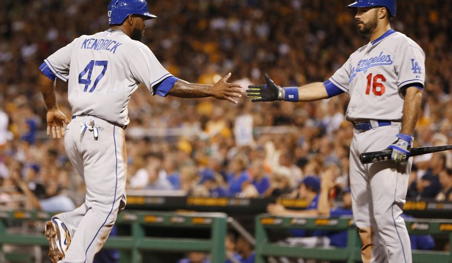 Los Angeles Dodgers' Howie Kendrick (47) is greeted by on deck batter Andre Ethier (16) after scoring on a hit by Adrian Gonzalez in the third inning of a baseball game against the Los Angeles Dodgers, Sunday, Aug. 9, 2015, in Pittsburgh. (AP Photo/Keith Srakocic)