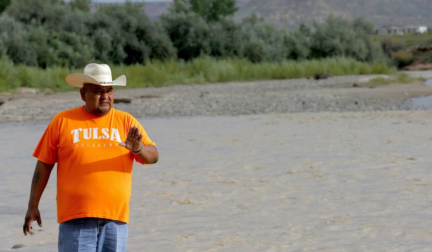 Navajo Nation Council Delegate Davis Filfred walks along the San Juan River, Tuesday, Aug. 11, 2015, in Montezuma Creek, Utah. A spill containing lead and arsenic from the abandoned Gold King Mine in Silverton, Colo., leaked into the Animas River, which flows into the San Juan River in Southern Utah, since last Wednesday. The spill was caused by a mining and safety team working for the EPA.  (AP Photo/Matt York)