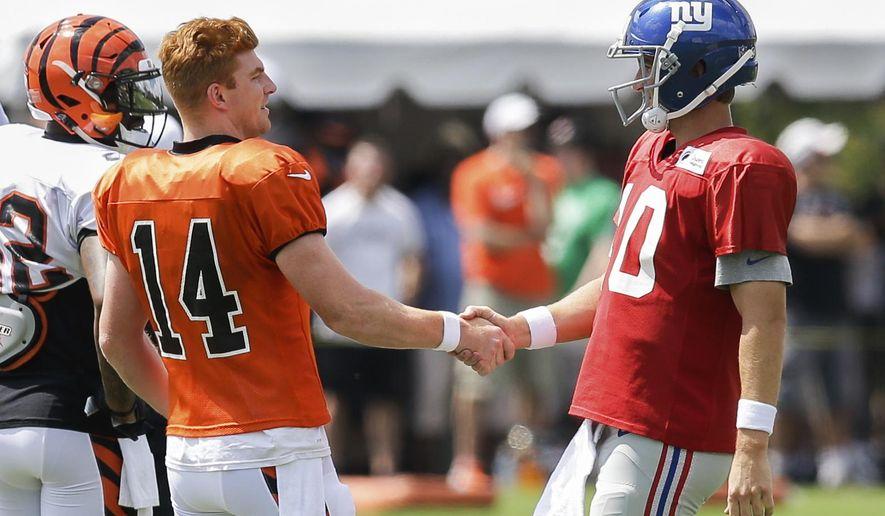 Cincinnati Bengals quarterback Andy Dalton, left, shakes hands with New York Giants quarterback Eli Manning during NFL football training camp, Tuesday, Aug. 11, 2015, in Cincinnati. (AP Photo/John Minchillo)