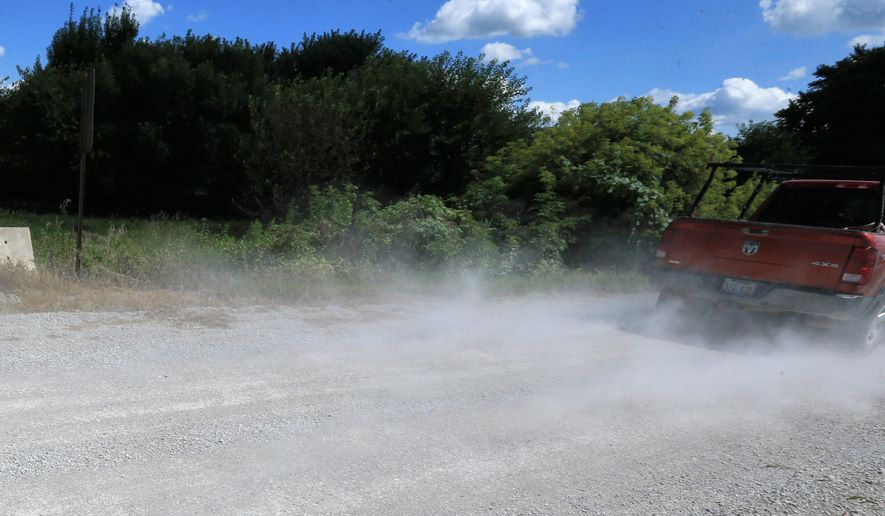 A vehicle kicks up dust on an unpaved section of 168th street, Tuesday, Aug. 11, 2015 in rural Gretna, Neb. Under a plan announced Tuesday by Nebraska Gov. Pete Ricketts, Nebraska counties and midsize cities are expected to receive an extra $3 million each year for street and bridge work through a program that allows them to swap federal dollars for state money to complete local projects. Sarpy County plans to use the newly announced program to upgrade 168th street, a gravel road with a county bridge just east of the fast-growing Omaha suburb. (AP Photo/Nati Harnik)