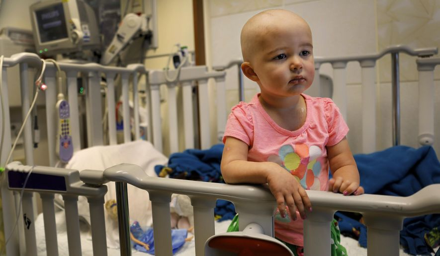 In this June 11, 2015 photo, Talia Pisano stands in her bed at Lurie Children's Hospital in Chicago. Talia is getting tough treatment for kidney cancer that spread to her brain. She's also getting a chance at having babies of her own someday. To battle infertility sometimes caused by cancer treatment, some children's hospitals are trying a futuristic approach: removing and freezing immature ovary and testes tissue, with hopes of being able to put it back when patients reach adulthood and want to start families. (AP Photo/Christian K. Lee)