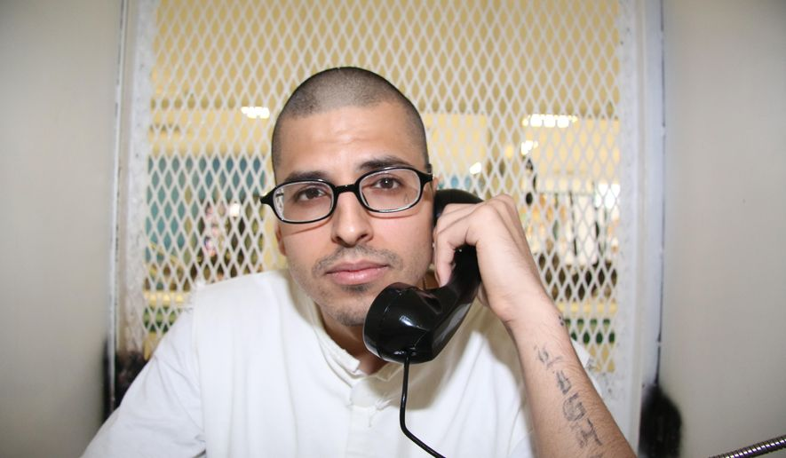 In this Aug. 5, 2015 photo, Daniel Lee Lopez, 27, speaks from a visiting cage outside death row at the Texas Department of Criminal Justice Polunsky Unit near Livingston, Texas. Lopez, who has been trying to speed up his execution since being sent to death row five years ago for a police lieutenant's killing, is scheduled to die Aug. 12, the first of two executions scheduled this week in Texas,  (AP Photo/Michael Graczyk)