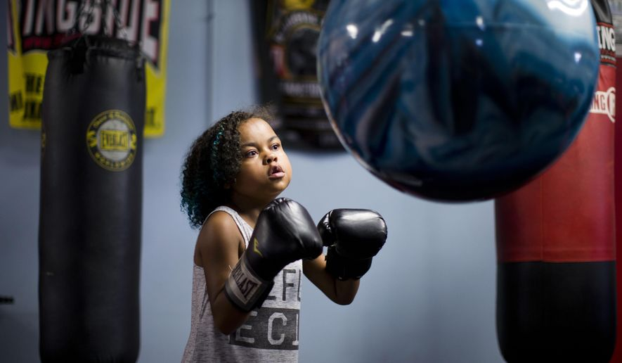 FILE - In this July 22, 2015, file photo, Kennedy Cunningham, 9, the daughter of boxer Steve Cunningham,  punches a bag as her father holds a media workout in Philadelphia. It's been a few months now, time that in the Cunningham household is best measured by the decreasing number of visits Kennedy Cunningham makes to the doctor. When her father, Steve Cunningham, returns to the ring this week his mind will be eased knowing his daughter is doing well after receiving a new heart. (AP Photo/Matt Rourke, File)