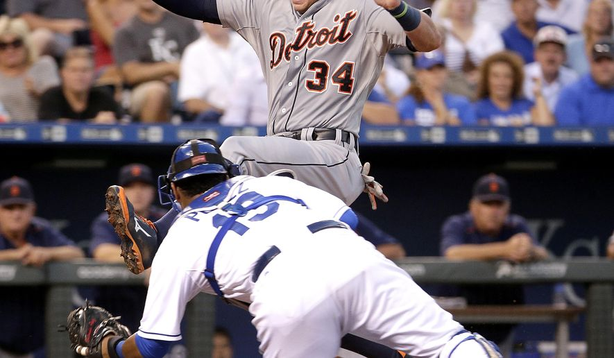 Detroit Tigers' James McCann (34) is tagged out at home by Kansas City Royals catcher Salvador Perez (13) as he tried to score on a double by Jefry Marte during the fourth inning of a baseball game Tuesday, Aug. 11, 2015, in Kansas City, Mo. (AP Photo/Charlie Riedel)
