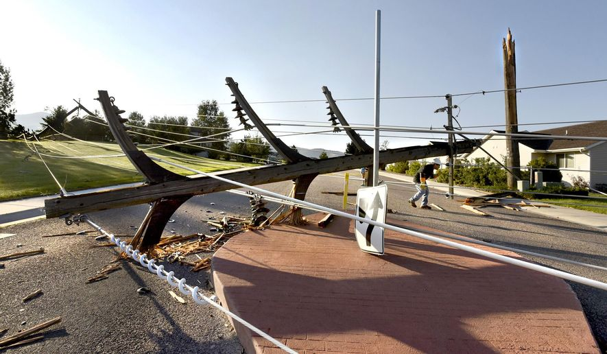 Joe Wulf, an engineer for Northwestern Energy ducks under a broken-off power pole lying in the middle of Christian Drive in Missoula, Mont., Tuesday, Aug. 11, 2015 while looking at the damage done Monday evening during an unusually strong windstorm Monday evening. The pole was one of several that were snapped off during the storm in the upper Linda Vista neighborhood. (Kurt Wilson/Missoulian via AP) MANDATORY CREDIT