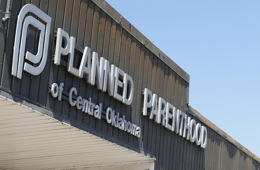 In this July 24, 2015, file photo, a sign at a Planned Parenthood Clinic is pictured in Oklahoma City. The furor on Capitol Hill over Planned Parenthood has stoked a debate about the use of tissue from aborted fetuses in medical research, but U.S. scientists have been using such cells for decades to develop vaccines and seek treatments for a host of ailments, from vision loss and neurological disorders to cancer and AIDS. (AP Photo/Sue Ogrocki/File)
