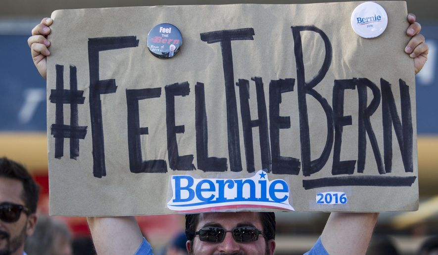 Frank Rothstein holds a sign before a rally for Democratic presidential candidate Sen. Bernie Sanders in Los Angeles. (AP Photo)
