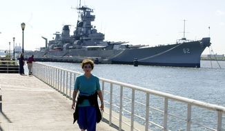 Josephine DeSousa of Cherry Hill, N.J., walks along the Camden, N.J. waterfront Thursday, Oct., 11, 2001 with The U.S.S. New Jersey Battleship looming in the background. The historic battleship will be begin its new role as a Camden tourist attraction on Monday. (AP Photo/Brian Branch-Price)