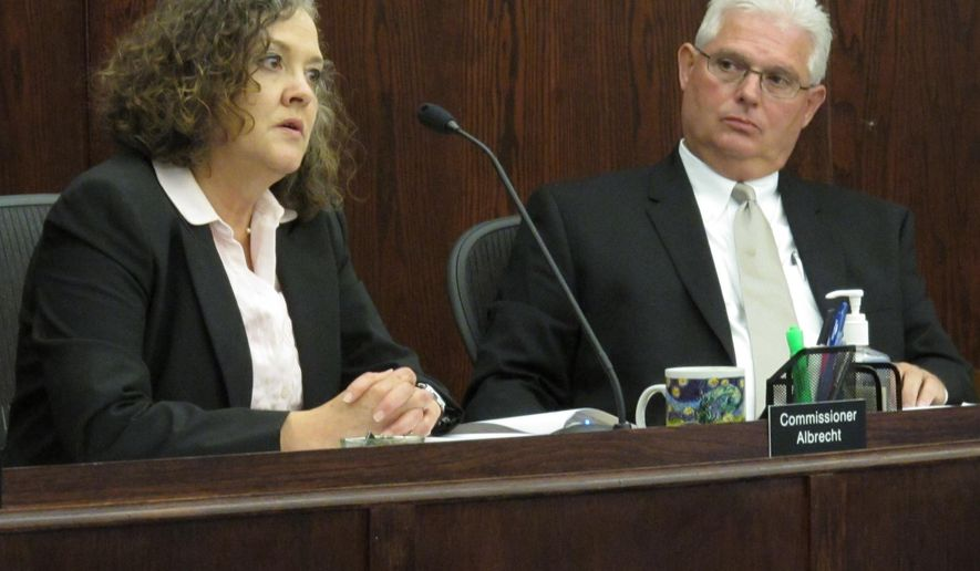 Kansas Corporation Commission Chairwoman Shari Feist Albrecht, left, discusses issues related to Kansas City Power & Light Co.'s rates, during a KCC meeting, as fellow Commissioner Pat Apple, right, watches, Tuesday, Aug. 11, 2015, in Topeka, Kan. The two KCC members disagree over how much to increase the utility's rates. (AP Photo/John Hanna)