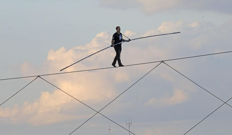 High-wire daredevil Nik Wallenda walks a tightrope above the  Milwaukee Mile Speedway at the Wisconsin State Fair in West Allis, Wis. Tuesday, Aug. 11, 2015. Wallenda completed his longest tightrope walk ever during the appearance at the Wisconsin State Fair. (Mike De Sisti/Milwaukee Journal-Sentinel via AP) MANDATORY CREDIT