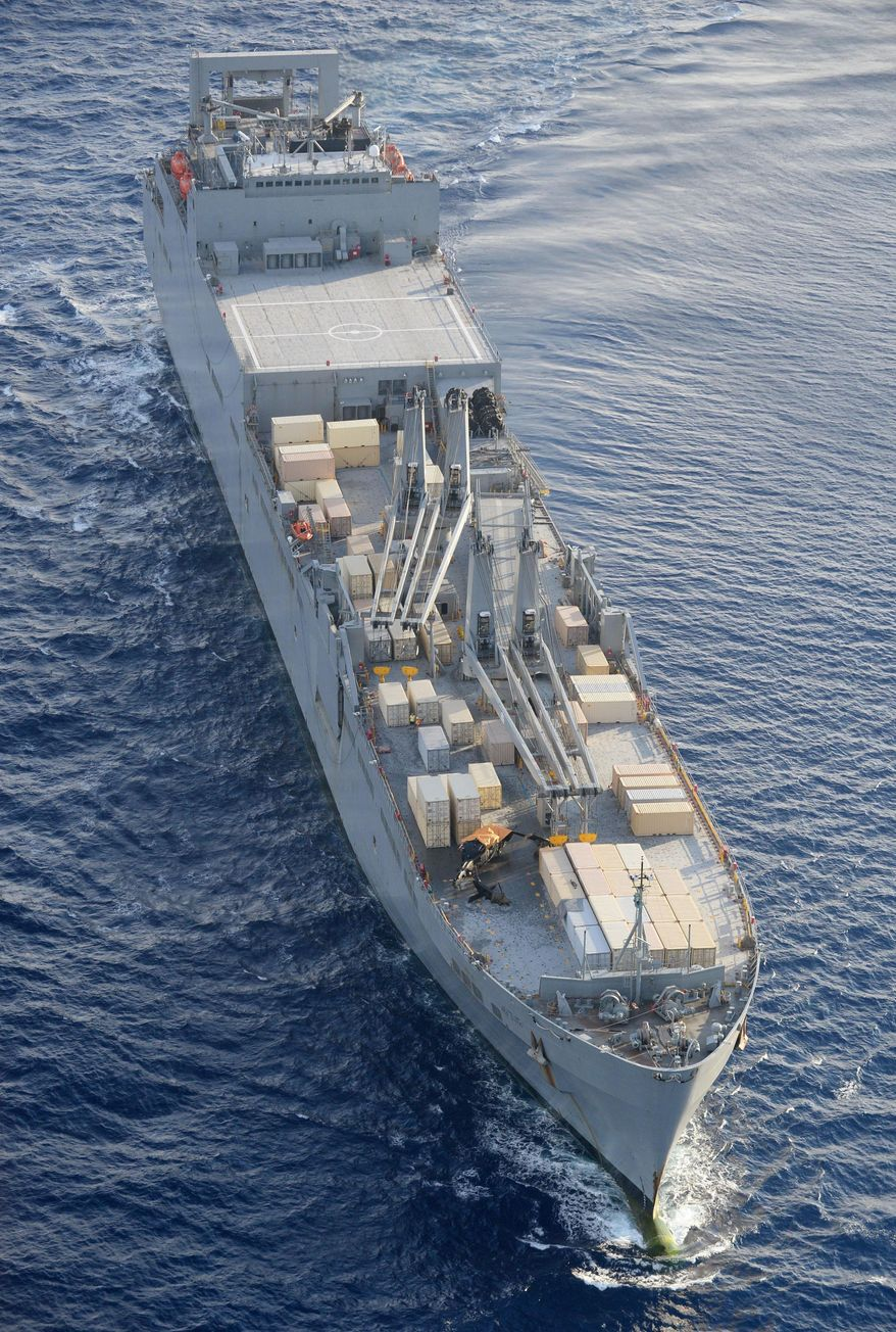 A crashed U.S. Army helicopter U-60 lies partially covered with a yellow sheet on the deck, bottom left, of the Navy cargo vessel USNS Red Cloud in the waters around 20 miles (30 kilometers) east of Japan's southern island of Okinawa Wednesday, Aug. 12, 2015. The helicopter crashed during a training mission while landing on the Navy ship, injuring several people and damaging the aircraft, officials said. (Ryosuke Uematsu/Kyodo News via AP) JAPAN OUT, CREDIT MANDATORY