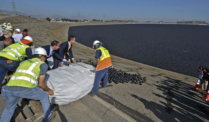 "In this Monday, Aug. 10, 2015 photo provided by the Los Angeles Department of Water and Power, Los Angeles Mayor Eric Garcetti, in suit at center rear, and LADWP workers deposit the final batch of over 90 million ""shade balls"" into the Los Angeles Reservoir in the Sylmar area of Los Angeles. The plastic balls were placed to protect water quality and to save 300 million gallons of water a year from evaporation. (Art Mochizuki/Los Angeles Department of Water and Power via AP)"