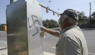 Sam Ferris washes away a swastika, Wednesday, Aug. 12, 2015 at Sholom Drive and Northwest Military Highway in San Antonio, that was spray painted on an electrical box. (/The San Antonio Express-News via AP)