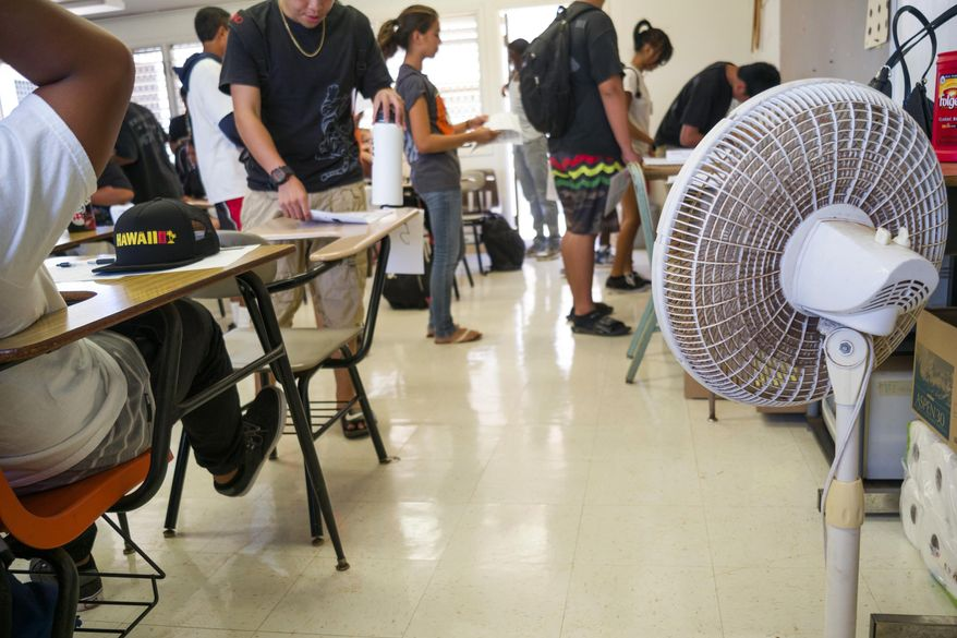 With only open windows and fans to cool the room down, students enter their non air conditioned classroom at Campbell High School, Monday, Aug. 3, 2015 in Ewa, Hawaii. Many public school classrooms across the Island are not equipped with AC, making it difficult for both teachers and students when the temperatures are high.  In Hawaii, which has been experiencing record high temperatures, school officials are weighing whether it makes sense to have heat days, where they cancel school because it's simply too hot.  (AP Photo/Marco Garcia)