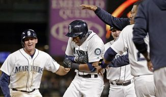 Seattle Mariners' Austin Jackson, center, is mobbed by teammates after hitting in the game-winning run against the Baltimore Orioles in the 10th inning of a baseball game Tuesday, Aug. 11, 2015, in Seattle. The Mariners won 6-5. (AP Photo/Elaine Thompson)