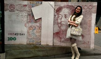 FILE - In this March 15, 2012 file photo, a Chinese woman poses for photos near a sculpture depicting a Chinese yuan note at an art district in Beijing, China. China devalued its tightly controlled currency on Tuesday, Aug. 11,2015,  following a slump in trade, triggering the yuan's biggest one-day decline in a decade.  The central bank said the yuan's 1.3 percent fall was due to a change aimed at making its exchange rate controls more market-oriented. But any change raises the risk of tensions with China's trading partners. (AP Photo/Ng Han Guan, File)