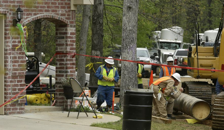 FILE - In this April 15, 2013, file photo, workers, right, examine a damaged section of oil pipe in a Mayflower, Ark., neighborhood after it was removed from the ground. A federal judge approved a $5 million settlement, Wednesday, Aug. 12, 2015, among the operators of an oil pipeline, the state of Arkansas and the federal government, finding that the deal to end claims stemming from a spill two years ago satisfied the public interest. (AP Photo/Danny Johnston, File)