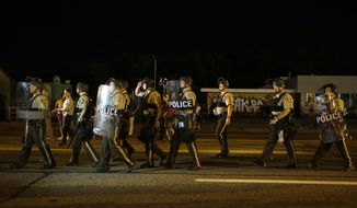 "Police walk around protesters as people gather along West Florissant Avenue in Ferguson, Mo., Tuesday, Aug. 11, 2015. The St. Louis suburb has seen demonstrations for days marking the anniversary of the death of 18-year-old Michael Brown, whose shooting death by a Ferguson police officer sparked a national ""Black Lives Matter"" movement. Tuesday was the fifth consecutive night a crowd gathered on West Florissant, the thoroughfare that was the site of massive protests and rioting after Brown was killed. (AP Photo/Jeff Roberson)"